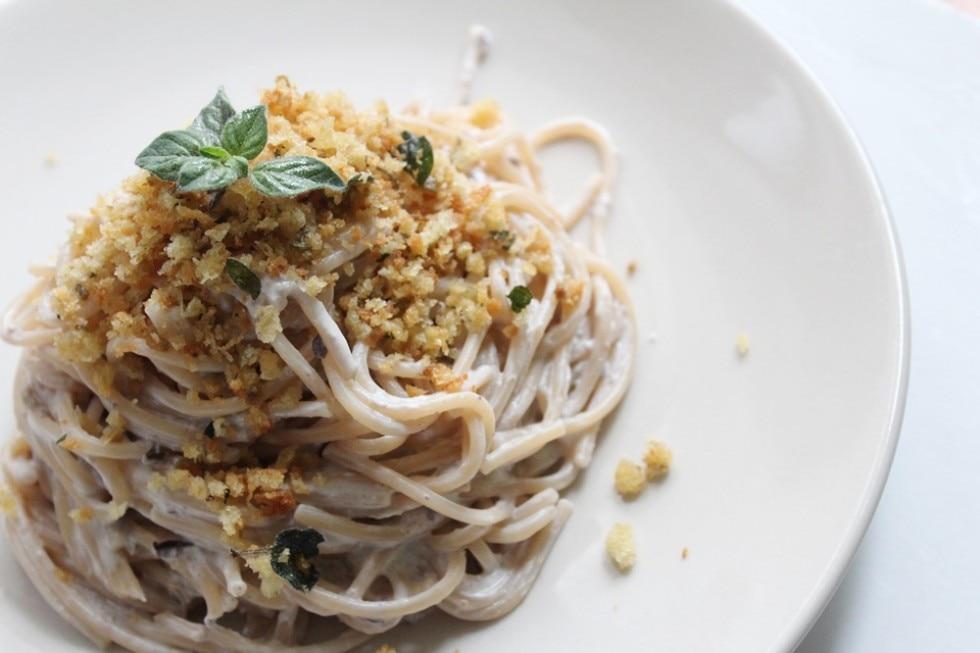 Spaghetti con crema di ricotta alle olive e briciole all'origano